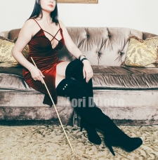 New York City professional switch dominatrix Lori DiLetto red velvet dress thigh high black suede boots cane