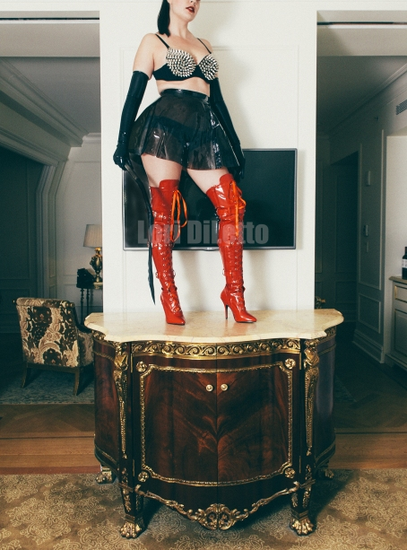 New York City dominatrix professional switch Lori DiLetto red thigh high boots spiked bra dragon tail whip